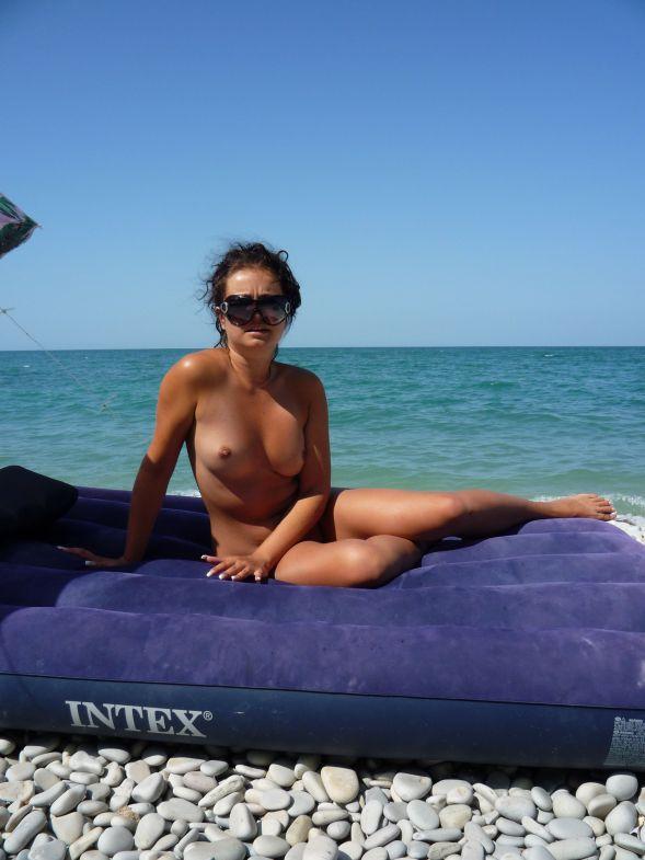Девушка плавает на надувном матрасе на пляже с нудистами - секс порно фото
