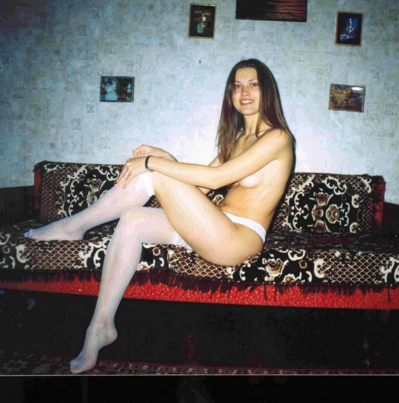 Молодая девица позирует голой в чулках на диване - секс порно фото