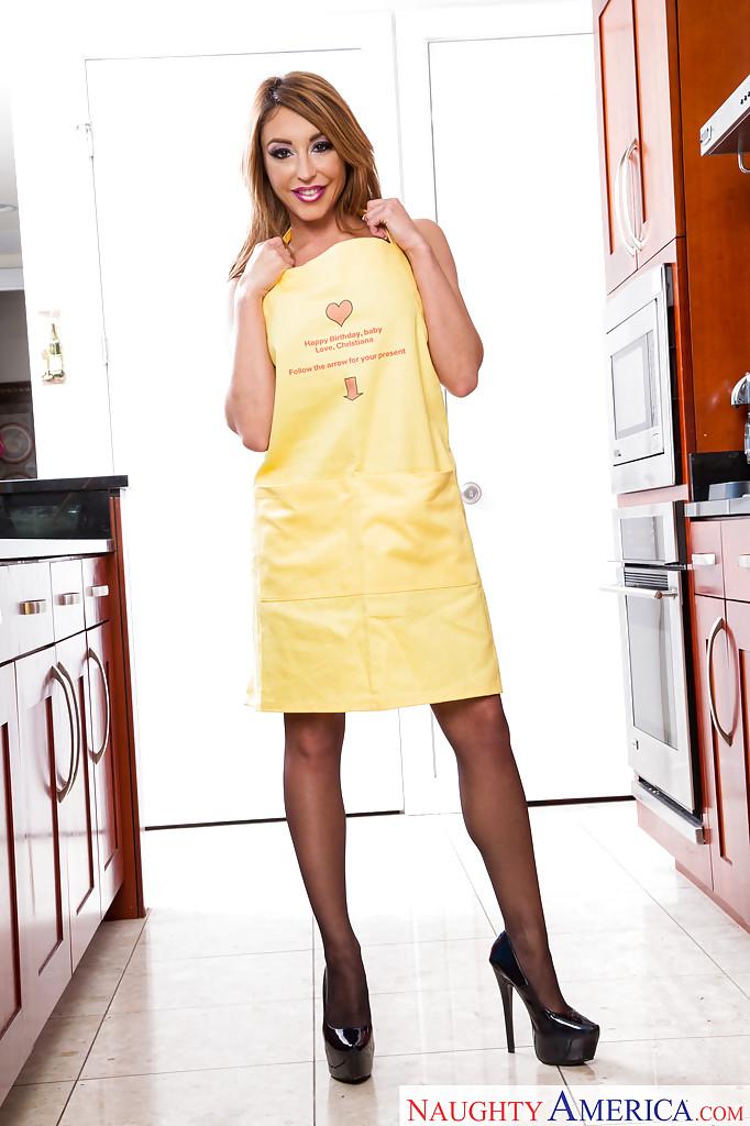Домохозяйка позирует на кухне в фартуке и черных чулках - секс порно фото