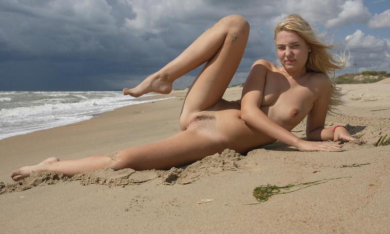 Стройная молодая девица голая позирует на пляже - секс порно фото