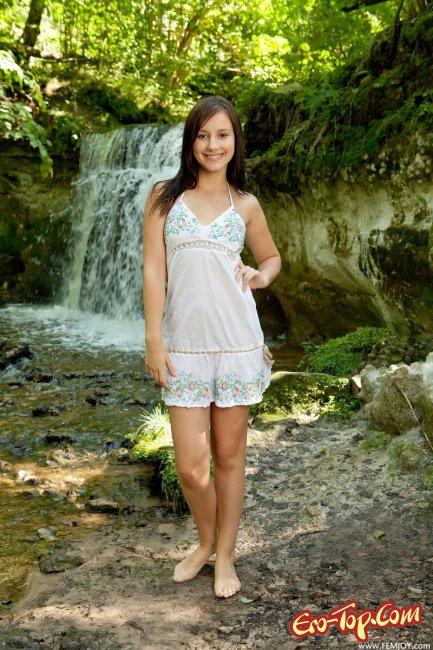Голая девушка на фоне водопада. Фото.