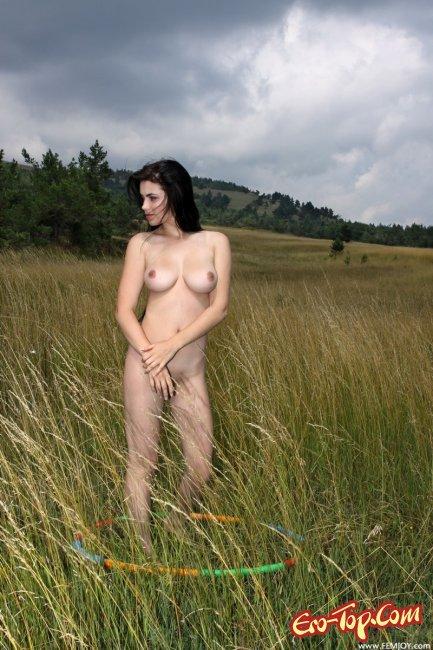 Голая девушка с обручем в поле. Фото.