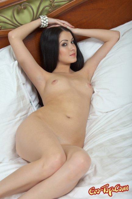 Голая брюнетка на кровати. Смотреть фото.