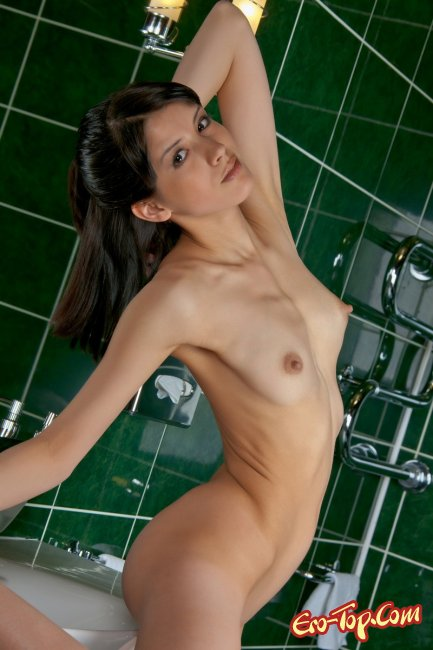Красивая голая девушка на кафеле в туалете. Фото.