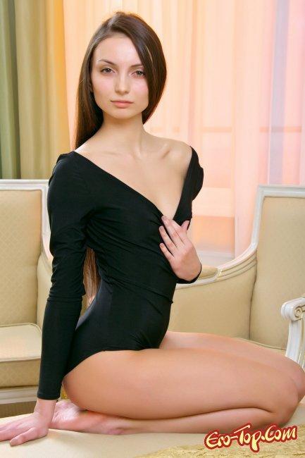 Девушка в чёрном боди раздевается. Фото эротика.